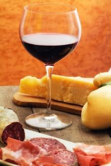 Sélection de fromage et jambon avec un verre de vin rouge