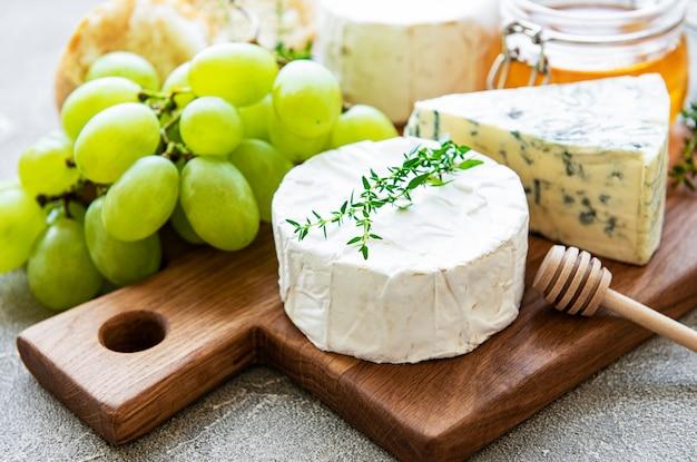 Sélection de fromages, miel et raisin sur une surface de béton gris