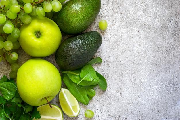 Sélection de fruits et légumes verts sur fond de béton gris