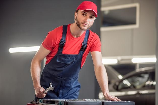 Sélection de pièces. séduisante jeune homme barbu en bonnet rouge avec une clé près de la boîte avec des pièces en atelier de réparation automobile