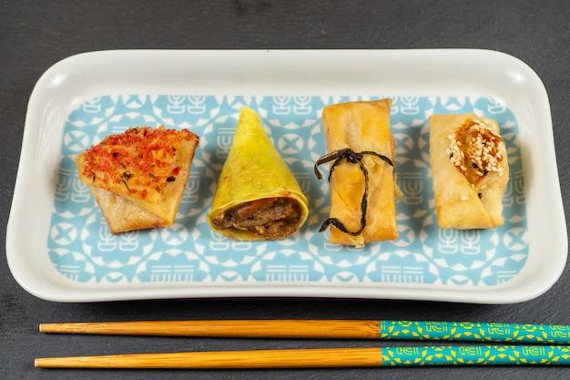 Sélection de plats asiatiques. cornets, paquets, paniers de gingembre et sauce soja, biscuits tikka, moulins à vent