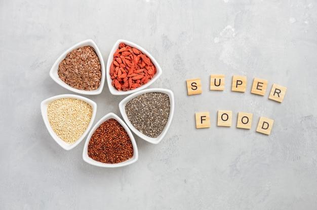 Sélection de super-aliments dans des bols blancs sur fond de béton gris.