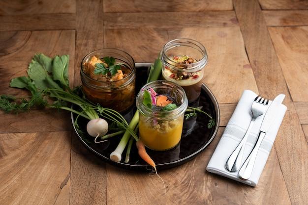 Sélection de trois 3 verrines de légumes du marché sur une table en bois, cuisine française, style bistrot
