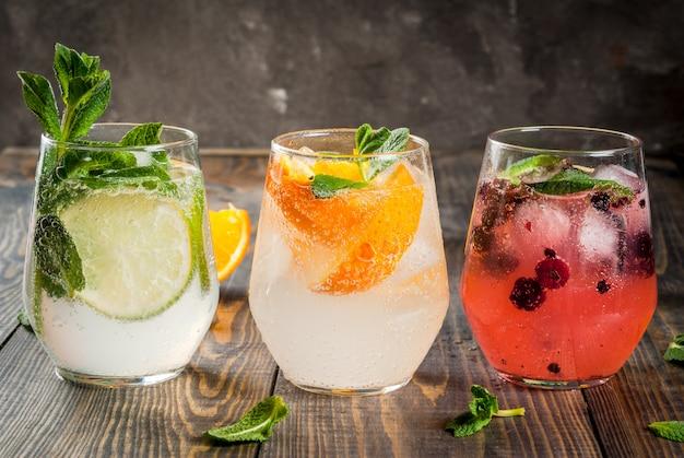 Sélection de trois sortes de gin tonic: aux mûres, à l'orange, au citron vert et aux feuilles de menthe. dans des verres sur un fond en bois rustique. espace copie