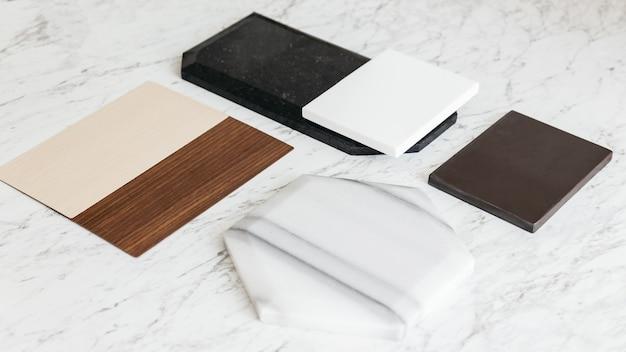Sélections d'échantillons de matériaux, y compris les carreaux de granit, les carreaux de marbre, les carreaux acoustiques, les stratifiés de bois de noyer et de frêne avec une plante sur une table en marbre.