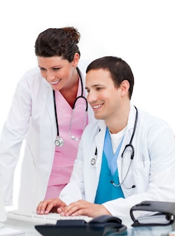 Selfassured médecin et infirmière travaillant à l'ordinateur