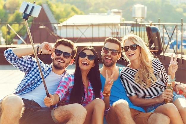 Selfie de l'amitié. groupe de jeunes heureux se liant les uns aux autres et faisant un selfie sur un téléphone intelligent tout en s'amusant sur le toit