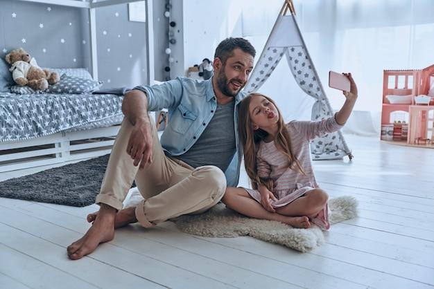 Selfie drôle. jeune père et sa petite fille prenant le selfie