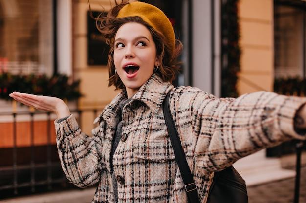 Selfie d'étudiante drôle en manteau à carreaux