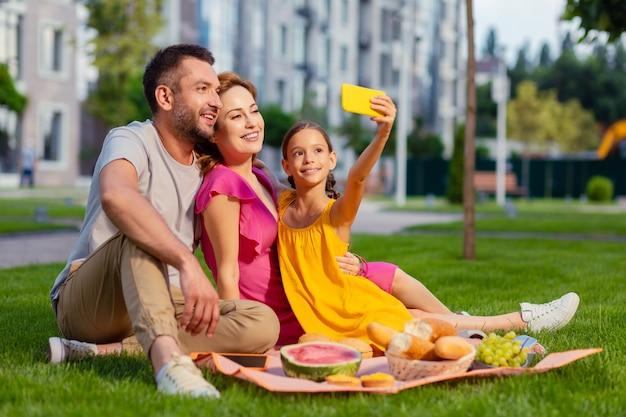 Selfie familial. joyeuse jolie fille tenant son smartphone tout en prenant un selfie avec la famille