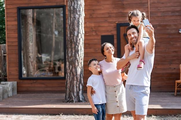 Selfie de famille avec des enfants ou passe un appel vidéo à des amis et des parents à l'aide d'un téléphone portable