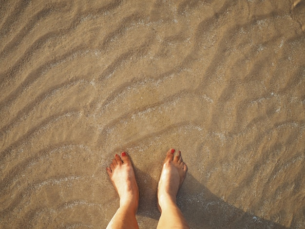 Selfie femme pieds sur fond de plage coucher de soleil beige sable été.
