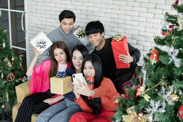Selfie de groupe de jeunes asiatiques avec des cadeaux à la maison pour célébrer le festival de noël. les adolescents thaïlandais célèbrent noël et le nouvel an. joyeux noël et joyeuses fêtes.