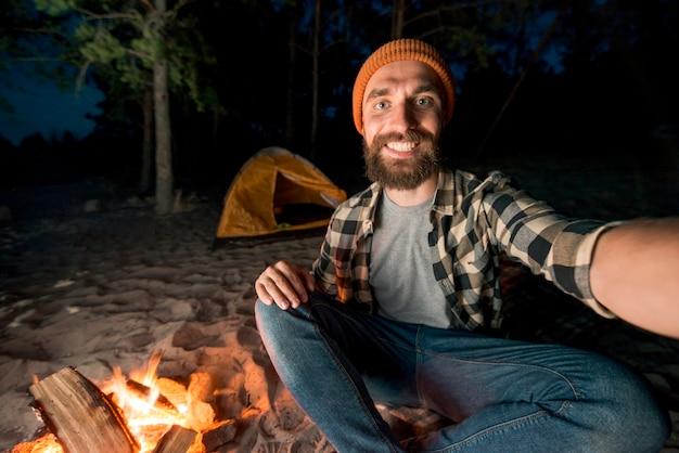 Selfie d'homme campant devant un camp de pompiers
