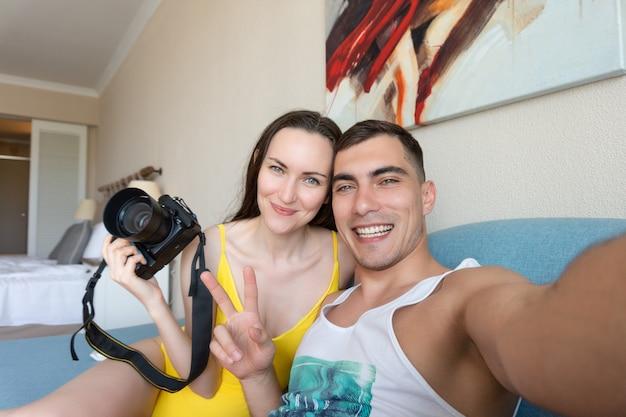 Selfie d'un jeune couple dans la chambre entre les mains d'un reflex numérique et un symbole de paix