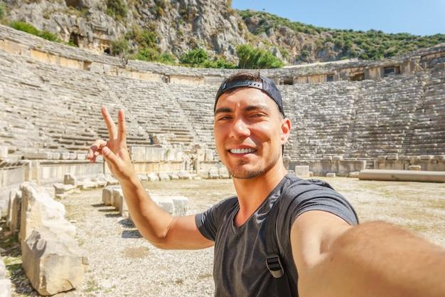 Selfie d'un jeune homme dans une casquette, montre le symbole de la paix