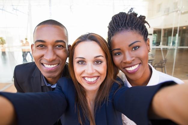 Selfie de joyeux amis d'affaires interculturels heureux