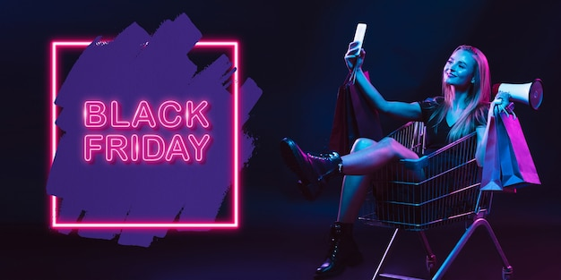 Selfie, mégaphone. portrait de jeune femme en néon sur fond de studio sombre. émotions humaines, vendredi noir, cyber lundi, achats, ventes, concept financier. espace de copie. publication transparente pour instagram.
