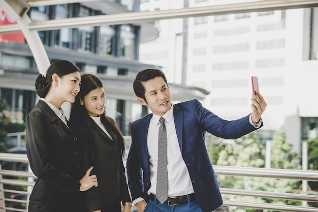 Selfie partenaires d'affaires sur smartphone.