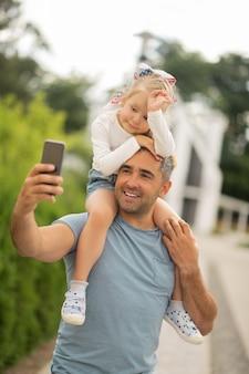 Selfie avec sa fille. bel homme d'affaires aux cheveux gris faisant un selfie avec sa fille