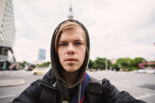 Selfies photo homme aux cheveux blonds sur le fond de la tour de télévision de berlin. voyage en allemagne