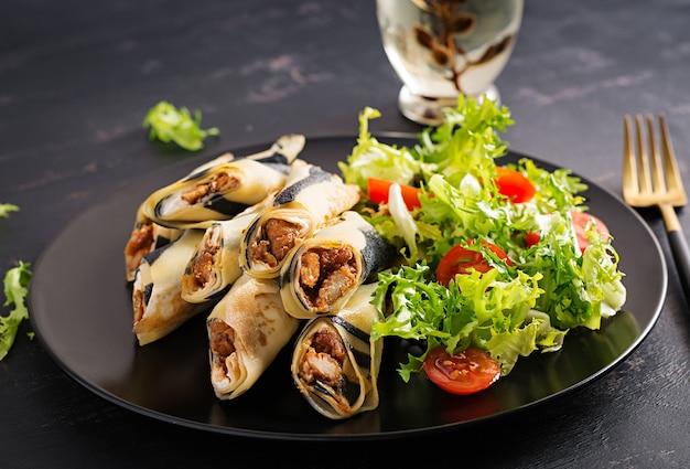Semaine des crêpes. le mardi gras. crêpes roulées farcies à la viande de poulet et aux légumes. crêpes salées.