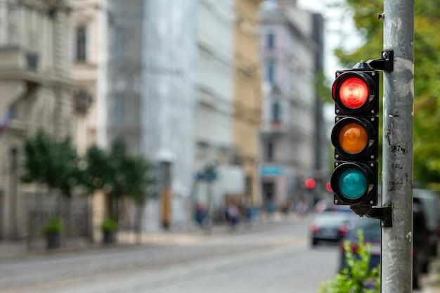 Sémaphore de contrôle du trafic avec lumière rouge sur un fond de ville défocalisé
