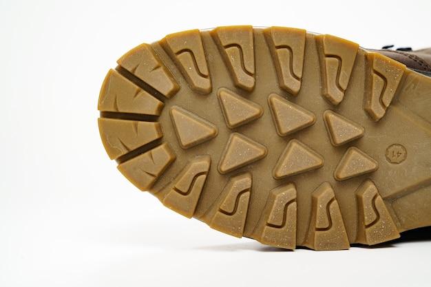 Semelle cannelée de chaussures pour hommes en cuir marron d'hiver sur fond blanc. achetez de belles chaussures modernes pour les voyages et le tourisme.