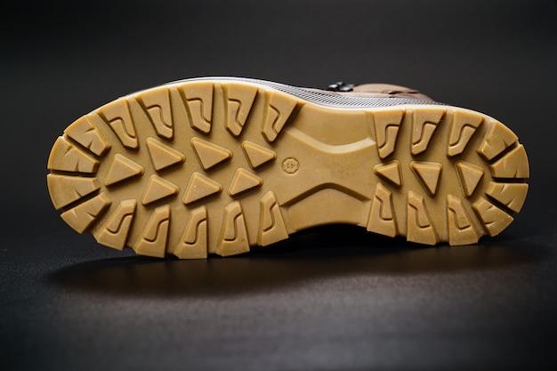 Semelle cannelée de chaussures pour hommes en cuir marron d'hiver sur fond noir. achetez de belles chaussures modernes pour les voyages et le tourisme.