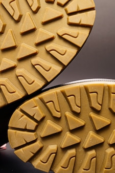 Semelle cannelée de chaussures pour hommes en cuir marron d'hiver sur fond noir.