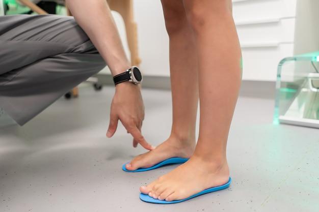 Semelle orthopédique. l'orthopédiste travaille avec le patient. clinique orthopédique. choix de semelles dans une clinique orthopédique. l'orthopédiste offre la semelle intérieure au patient soins des pieds