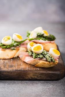 Sendwich frais avec du jambon, des asperges et des œufs de caille