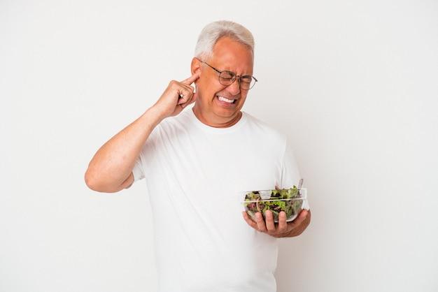 Senior american man eating salad isolé sur fond blanc couvrant les oreilles avec les mains.