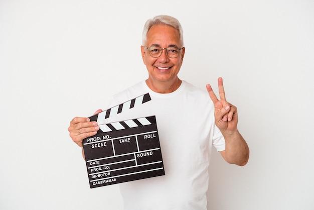 Senior american man holding a clap isolé sur fond blanc montrant le numéro deux avec les doigts.