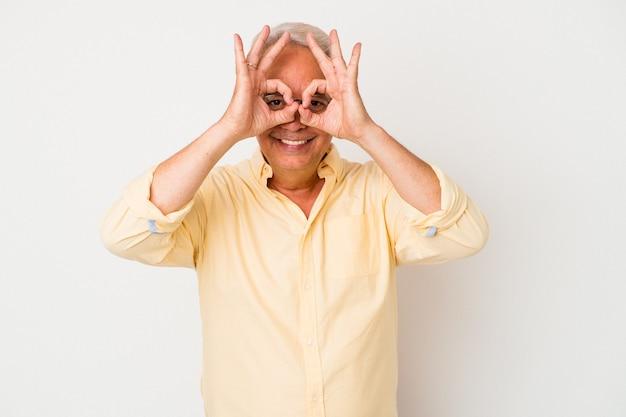 Senior american man isolé sur fond blanc excité en gardant le geste ok sur les yeux.