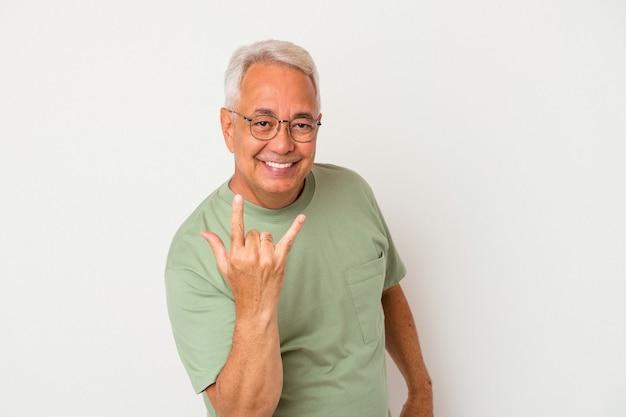 Senior american man isolé sur fond blanc montrant rock geste avec les doigts