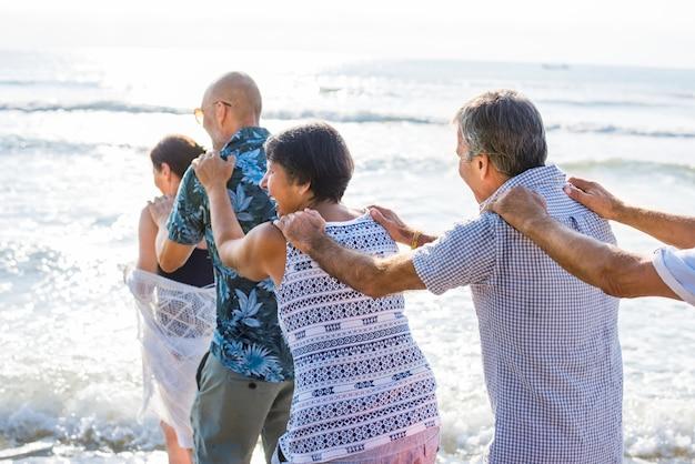 Senior amis jouant à la plage