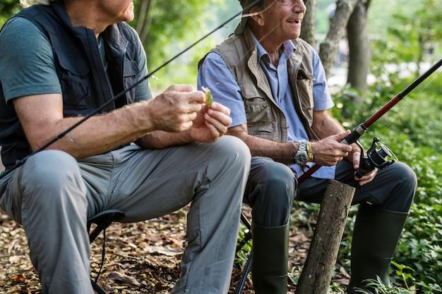 Senior amis pêchant au bord du lac
