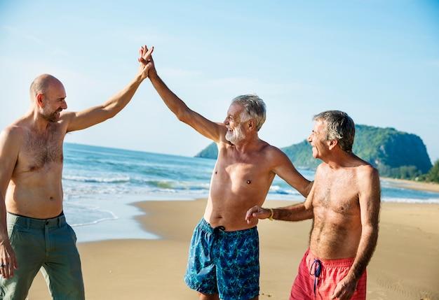 Senior amis s'amusant à la plage