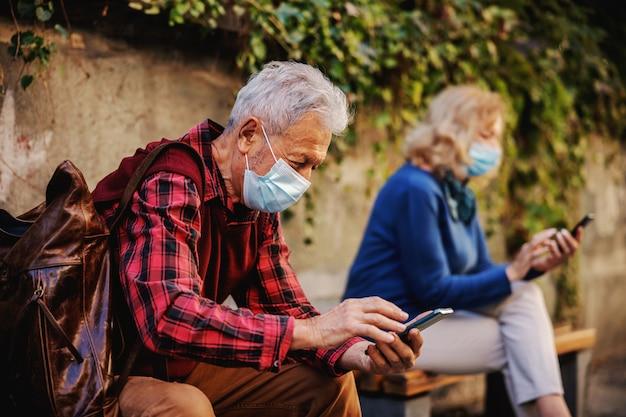 Senior an avec masque de protection assis sur le banc à l'extérieur et à l'aide de téléphone portable.