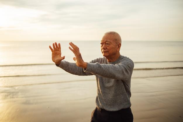 Senior asiatique pratiquant le tai chi et le yoga pose sur le lever du soleil sur la plage
