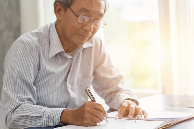 Senior asiatique travaillant écrit à la main ou signer un contrat d'assurance pour le futur concept.