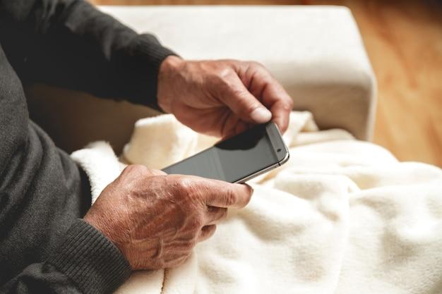 Senior assis sur un canapé avec téléphone portable à la main