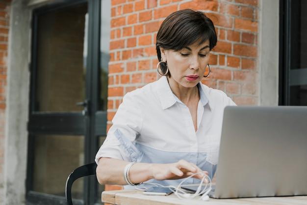Senior assis à l'extérieur avec un ordinateur portable