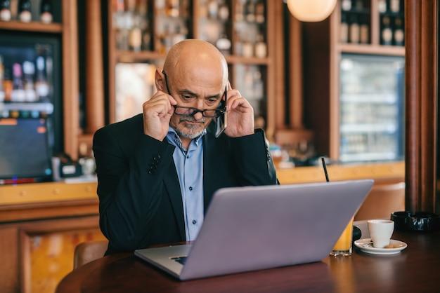 Senior barbu en costume à l'aide d'un téléphone intelligent et d'un ordinateur portable assis dans une cafétéria.