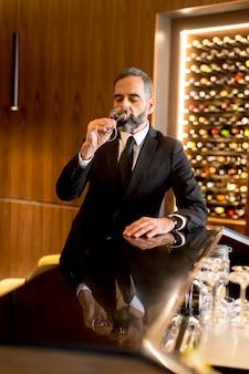 Senior bel homme buvant du vin rouge