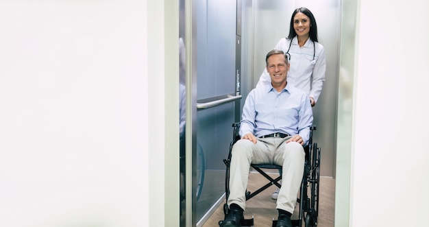 Senior bel homme en fauteuil roulant se déplace à l'hôpital avec l'aide d'un personnel médical spécial