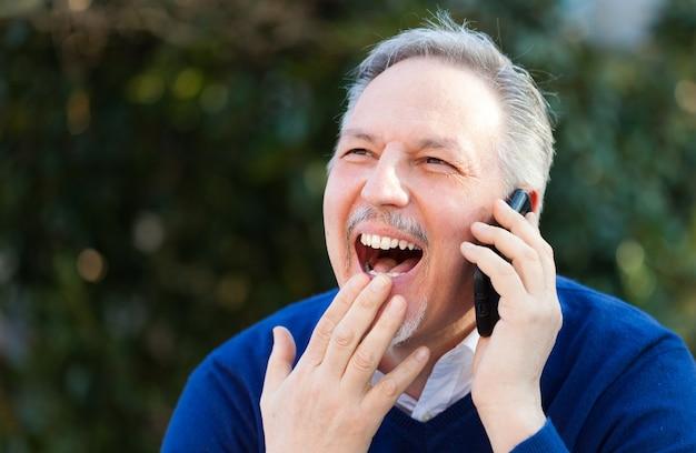 Senior bel homme parlant au téléphone dans un parc