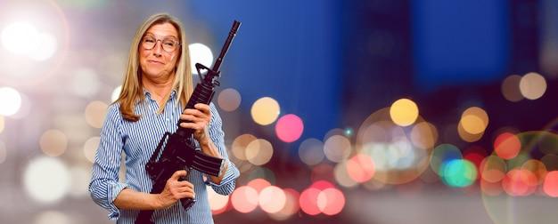 Senior belle femme avec un fusil. concept de conflit