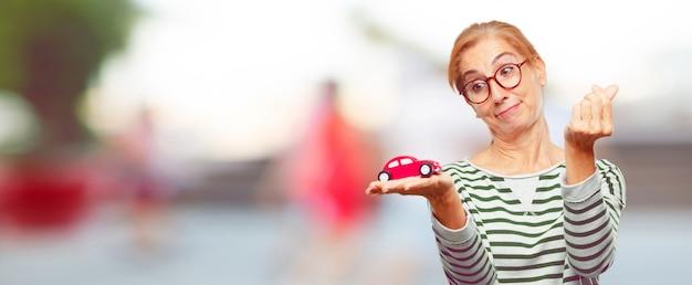 Senior belle femme avec un modèle de voiture rouge